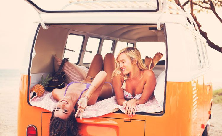Girls in a van on the beach laughing