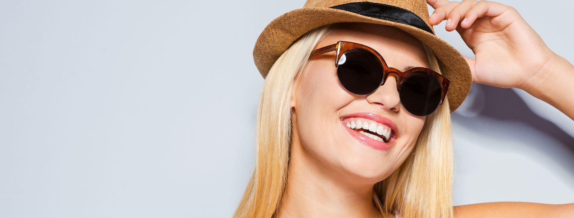 Woman with hat and sunglasses using Sunsafe Rx